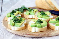 Sandwich. Es with avocado and pesto sauce on a wooden board Royalty Free Stock Photography