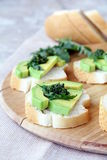 Sandwich. Es with avocado and pesto sauce on a wooden board Stock Image