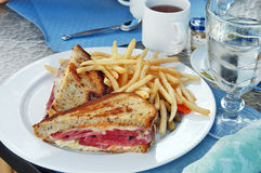Sandwich. The rare beef sandwich with French fries, cornichon, ice water and hot tea Stock Photos
