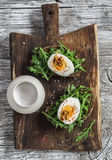 Sandwich with arugula, boiled egg and mustard on a wooden board. Healthy breakfast Stock Photo