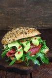 Sandwich with arugula, salami and avocado Stock Photography