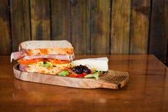 Sandwich auf hölzernem Brett mit Briekäse und Salat Lizenzfreie Stockfotos