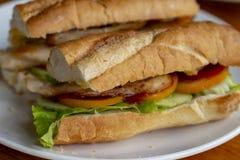 Sandwich avec de la salade et des tomates sur la photo blanche de plan rapproché de plat Baguette française avec de la salade sur Photos libres de droits
