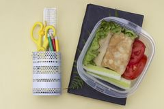 Sandwich avec des légumes dans un conteneur, un repas scolaire, des crayons multicolores et un livre sur un fond jaune, vue supér images stock