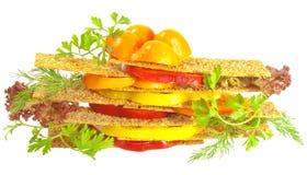 Sandwich avec des parts de tomate et de poivre d'isolement Photographie stock libre de droits