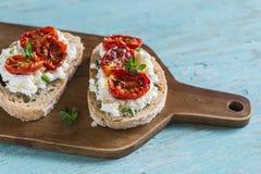 Sandwich avec du fromage de chèvre, les tomates séchées au soleil et le thym, servis sur le conseil Photographie stock libre de droits