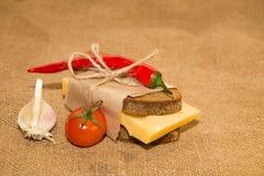 Sandwich avec du fromage enveloppé dans le papier, les tomates-cerises et le garli Images stock