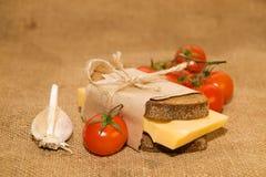 Sandwich avec du fromage enveloppé dans le papier, les tomates-cerises et le garli Photos libres de droits