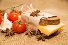 Sandwich avec du fromage enveloppé dans le papier, les tomates-cerises et le garli Image libre de droits