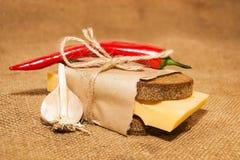 Sandwich avec du fromage enveloppé en papier, poivre de piment et ail o Photographie stock