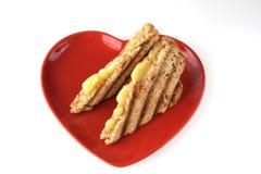 Sandwich avec du fromage fondu de la plaque de forme de coeur Images stock