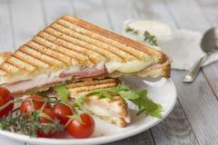 Sandwich avec du jambon et des tomates sur le fond en bois photo libre de droits