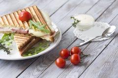 Sandwich avec du jambon et des tomates sur le fond en bois photos stock