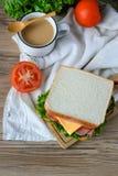 Sandwich avec du jambon, fromage et légumes et café chaud sur la table en bois Image libre de droits