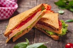 Sandwich avec du jambon, le fromage, des tomates et des feuilles de laitue sur la table rustique en bois photographie stock