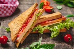 Sandwich avec du jambon, le fromage, des tomates et des feuilles de laitue sur la table rustique en bois image stock