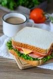 Sandwich avec du jambon, le fromage et des légumes sur la table en bois Photos stock