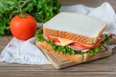Sandwich avec du jambon, le fromage et des légumes sur la table en bois Photo stock