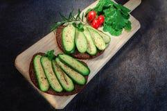 Sandwich avec l'avocat, l'oeuf et la tomate-cerise aspermes sur la planche à découper Avocat sans toute graine Avocat de cocktail Photo stock