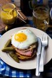 Sandwich avec la choucroute, le jambon et les oeufs au plat Photographie stock libre de droits