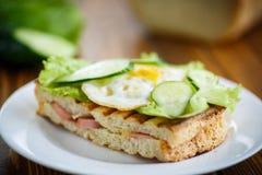 Sandwich avec la saucisse, le fromage, la laitue et les oeufs Photo stock