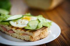 Sandwich avec la saucisse, le fromage, la laitue et les oeufs Photos stock
