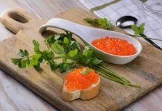 Sandwich avec le caviar rouge sur une planche à découper en bois Image libre de droits