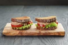 Sandwich avec le thon et les légumes sur le pain de seigle Photo stock