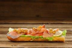 Sandwich avec les poissons, les tomates et la moutarde rouges Photo stock