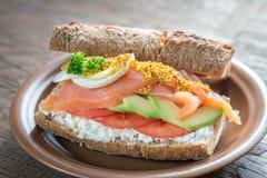 Sandwich avec les saumons, l'avocat et les oeufs Photographie stock