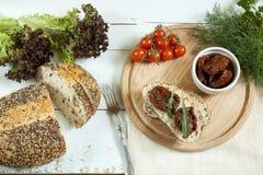 Sandwich avec les tomates et l'arugula séchés au soleil, tomates séchées au soleil, tomates fraîches, moules Images libres de droits