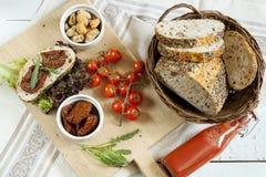 Sandwich avec les tomates et l'arugula séchés au soleil, tomates séchées au soleil, tomates fraîches, moules Photos libres de droits