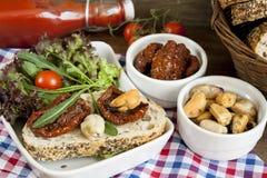 Sandwich avec les tomates et l'arugula séchés au soleil, tomates séchées au soleil, tomates fraîches, moules Photographie stock