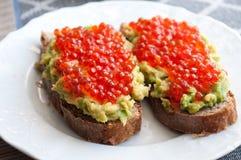 Sandwich with avocado and caviar. Grain bread with avocado paste and salmon caviar Royalty Free Stock Photo