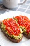Sandwich with avocado and caviar. Grain bread with avocado paste and salmon caviar Stock Image