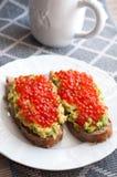 Sandwich with avocado and caviar. Grain bread with avocado paste and salmon caviar Stock Photo