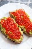 Sandwich with avocado and caviar. Grain bread with avocado paste and salmon caviar Stock Photos