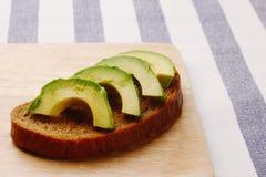 Sandwich with avocado on dark rye bread made with fresh sliced avocado royalty free stock photos