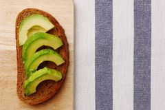 Sandwich with avocado on dark rye bread made with fresh sliced avocado royalty free stock photography
