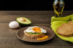 Sandwich with avocado and a fried egg on a brown plate on a rustic wood and table bread on green kitchen towel. Sandwich with avocado and a fried egg on a brown Royalty Free Stock Image