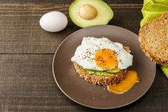 Sandwich with avocado and a fried egg on a brown plate on a rustic wood and table bread on green kitchen towel. Sandwich with avocado and a fried egg on a brown Stock Photo