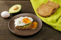Sandwich with avocado and a fried egg on a brown plate on a rustic wood and table bread on green kitchen towel. Sandwich with avocado and a fried egg on a brown Royalty Free Stock Photo