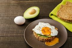 Sandwich with avocado and a fried egg on a brown plate on a rustic wood and table bread on green kitchen towel. Sandwich with avocado and a fried egg on a brown Royalty Free Stock Photography