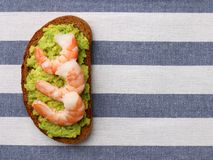 Sandwich with avocado guacomole and seafood srimp on light background royalty free stock photography