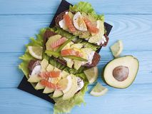 Sandwich with avocado red fish lunch lemon blue wooden appetizer rustic. Sandwich with avocado lemon red fish rustic on blue wooden appetizer lunch Royalty Free Stock Photo