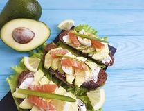 Sandwich with avocado red fish blue wooden appetizer rustic. Sandwich with avocado red fish rustic  on blue wooden appetizer Royalty Free Stock Photos