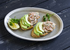 Sandwich with avocado, salmon and whole wheat bread on an oval plate on a dark wooden surface Stock Image