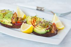 Sandwich with avocado, sprouts, tomato, light background Royalty Free Stock Image