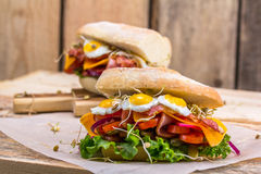 A sandwich with bacon, cheese and fried quail eggs. A sandwich with fresh vegetables and herbs on a wooden background. Stock Images