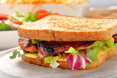 Sandwich with bacon cheese and vegetables on wooden background Royalty Free Stock Images